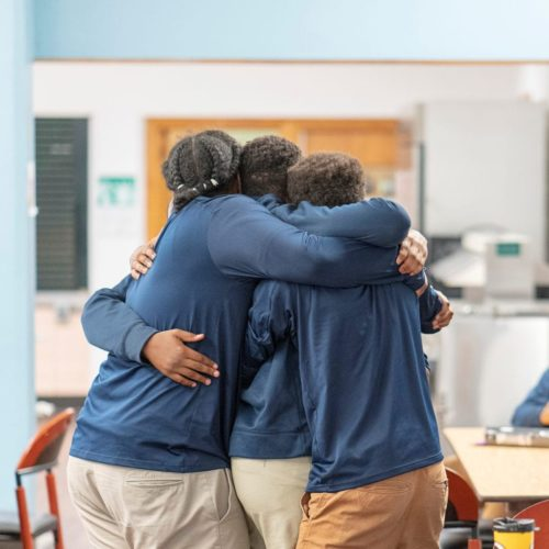 Young men embracing a hug to showcase a bond in brotherhood