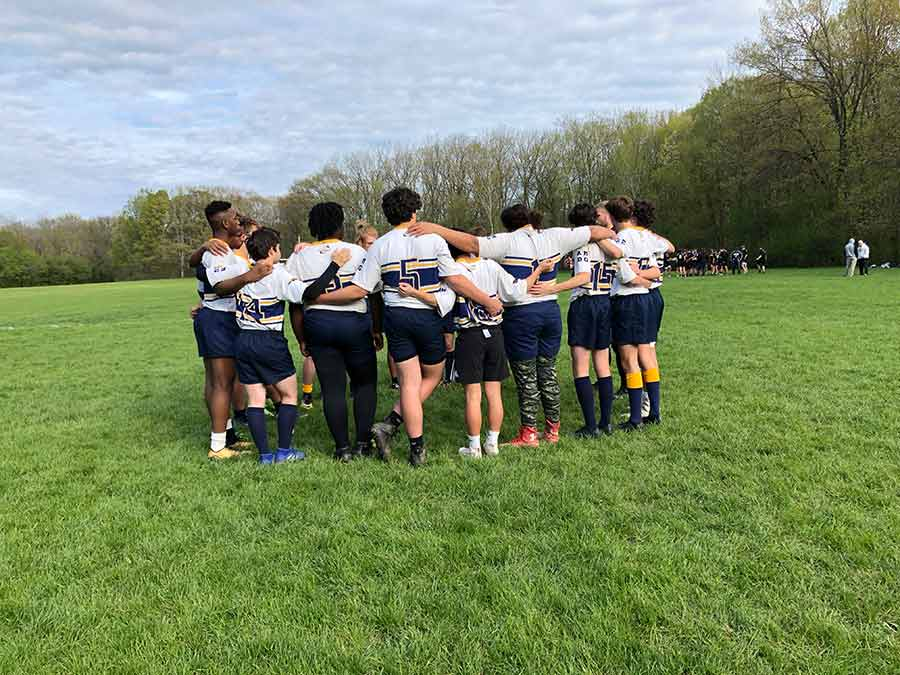 Kingdom Prep Rugby team hugging.